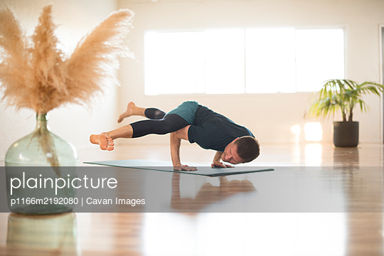A guy in hurdlers pose during yoga. - p1166m2192080 by Cavan Images