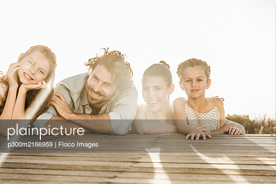Portrait of family lying on terrace at sunset - p300m2166959 by Floco Images