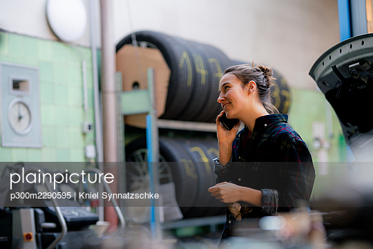 Female mechanic looking away while talking on smart phone at workshop - p300m2290595 by Kniel Synnatzschke