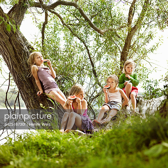 Girls eating watermelon in tree by lake - p42916730f by Henrik Weis