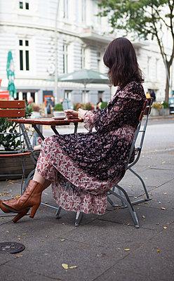 Frau sitzt im Café an Straße - p045m2027620 von Jasmin Sander