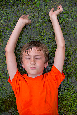 Boy lying in flooded grass - p1169m2108487 by Tytia Habing