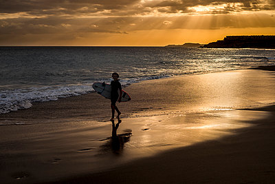 Spain, Tenerife, boy carrying surfboard on the beach at sunset - p300m1189137 by Simona Pillola