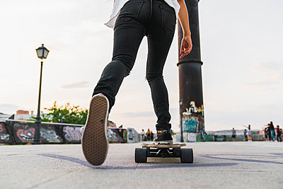 Close-up of young woman riding skateboard in the city - p300m2060996 by Kike Arnaiz