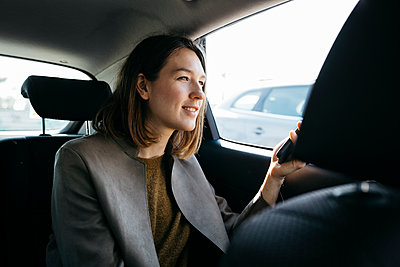 Smiling woman sitting in back seat of a car holding cell phone - p300m2083522 by Josep Rovirosa