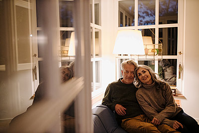 Portrait of senior couple relaxing on couch at home at night - p300m2155258 by Gustafsson