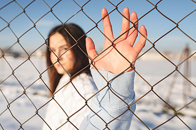 Young woman stretching hand toward fence while standing outdoors - p300m2252648 by Jose Carlos Ichiro