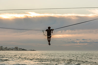 Man slacklining and waterlining during sunrise in Leblon Beach, Rio de Janeiro, Brazil - p343m1543666 by Vitor Marigo