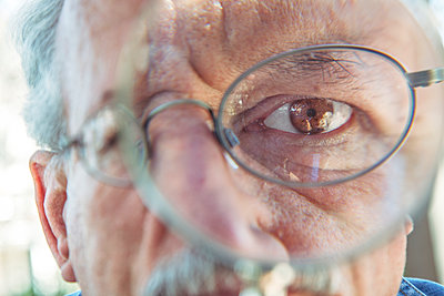 Eye of older man using magnifying glass - p555m1219625 by DreamPictures