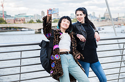 Two young stylish women taking smartphone selfie on millennium footbridge, London, UK - p924m1513523 by Bonfanti Diego