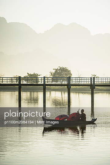 Mountains and bridge reflected in still lake, Hpa an, Kayin, Myanmar,Hpa An, Kayin, Myanmar - p1100m2084194 by Mint Images