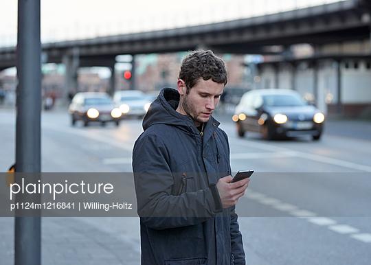 Mann mit Smartphone an Straße - p1124m1216841 von Willing-Holtz