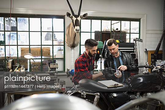 Motorcycle mechanics with clipboard examining part, fixing motorcycle in auto repair shop