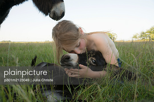 Girl hugging and kissing baby donkey in grass - p301m2123049 by Julia Christe
