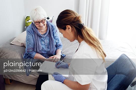Nurse with elderly woman at home - p312m2299642 by Plattform