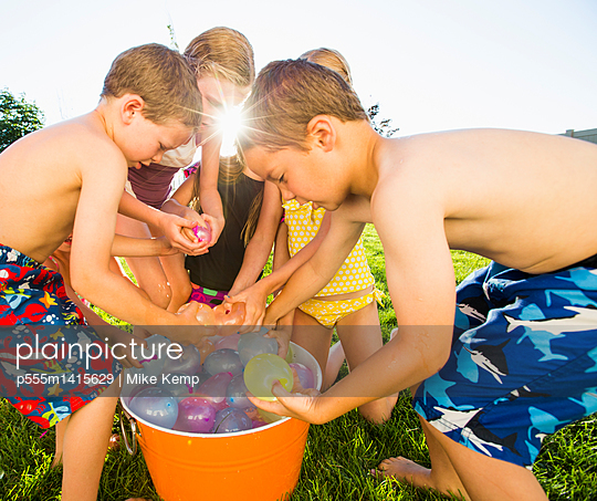 Caucasian children playing with water balloons in backyard - p555m1415629 by Mike Kemp