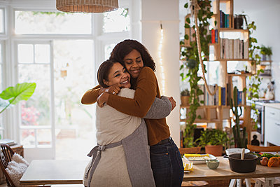 Happy mother and daughter hugging at home - p1023m2262336 by Tom Merton