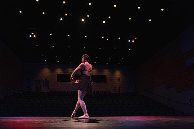Ballet dancer dancing on stage at theatre - p1315m1566751 by Wavebreak