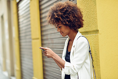 Smiling young woman with curly hair looking at cell phone - p300m2004789 von Javier Sánchez Mingorance