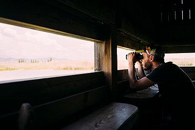 Man birdwatching with binoculars from a viewing tower - p300m2058811 von Gemma Ferrando
