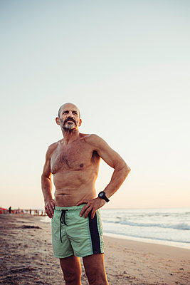 Man with hand on hip standing at beach - p300m2221132 by Eugenio Marongiu