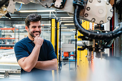 Smiling male worker with hand on chin looking at robotic arm in manufacturing industry - p300m2225322 by Daniel Ingold