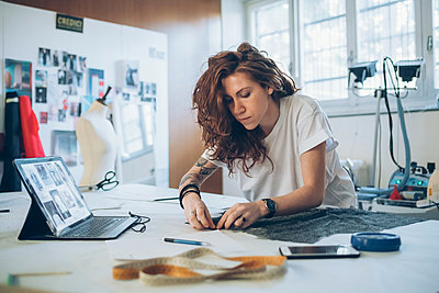 Fashion designer pinning fabric cutouts - p429m2058370 by Eugenio Marongiu