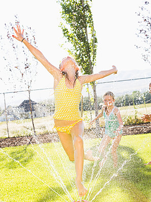 Caucasian girls playing in sprinkler in backyard - p555m1415622 by Mike Kemp
