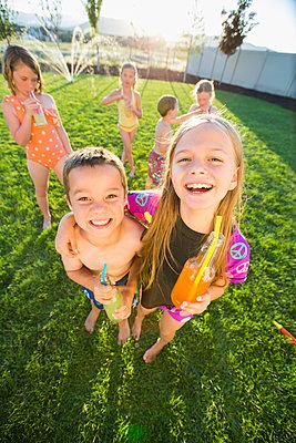 Caucasian children drinking soda in backyard - p555m1415634 by Mike Kemp