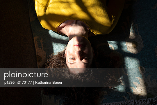 Woman in selfquaratine lying on carpet - p1295m2173177 by Katharina Bauer