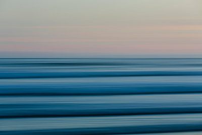 Ocean waves and the view to the horizon over the sea at dusk from the beach.  - p1100m1216314 by Mint Images