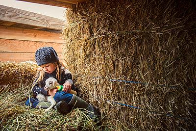 Cute girl feeding milk to lamb while sitting on hay in barn - p1166m2024813 by Cavan Images