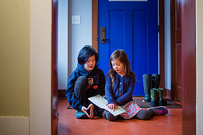 two children sit in the foyer of their home reading a book together - p1166m2096051 by Cavan Images