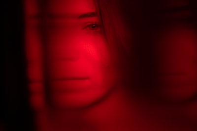 Blurred view of female face bathed in red light - p1321m2210600 by Gordon Spooner