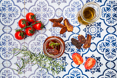 Glass of pickled dried tomatoes and ingredients on tiles - p300m1191784 by Larissa Veronesi