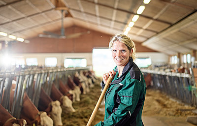Portrait of smiling female farmer in stable on a farm - p300m1567817 by Christian Vorhofer