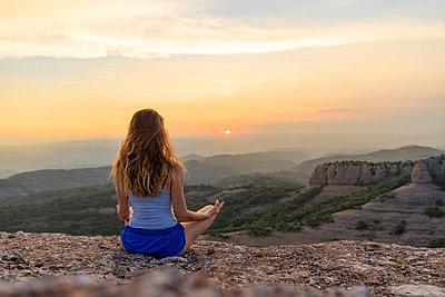 Spain, Catalonia, Sant Llorenc del Munt i l'Obac, Woman meditating in the mountains - p300m2028689 von VITTA GALLERY