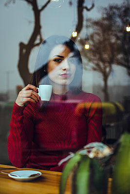 Portrait of beautiful young woman with cup of coffee behind windowpane in a cafe - p300m2102054 by Aitor Carrera Porté