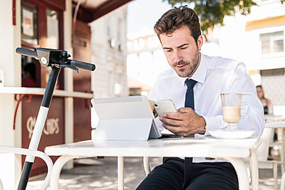 Young businessman using tablet and mobile phone at a cafe in the city, Lissabon, Portugal - p300m2144886 von Uwe Umstätter