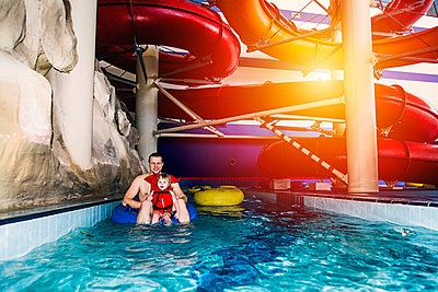 Caucasian father and daughter swimming under water park slide - p555m1306024 by Aleksander Rubtsov