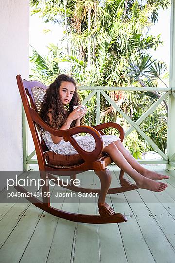 Mädchen auf Veranda mit Porzellantasse - p045m2148155 von Jasmin Sander