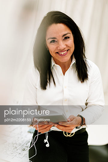 Smiling businesswoman looking at camera - p312m2208159 by Plattform