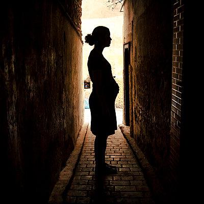 Pregnant woman in dark alley - p1118m1539792 by Tarik Yaici