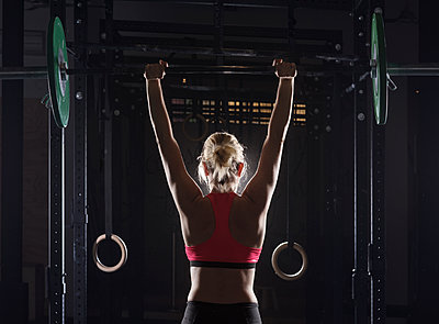 Rear view of female athlete picking barbell at gym - p1166m1154112 by Cavan Images