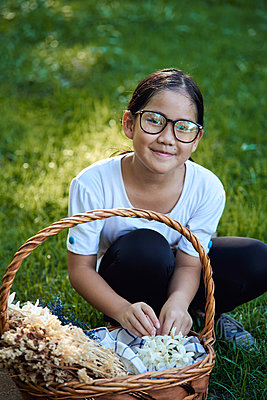 Portrait a girl picking flowers in the park - p1166m2216936 by Cavan Images