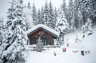 Austria, Altenmarkt-Zauchensee, snowman, sledges and Christmas tree at wooden house in snow - p300m2042016 by Hans Huber