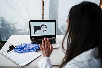Female medical professional waving at senior patient during video call at desk - p300m2265715 by Eva Blanco