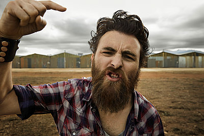 Angry man with full beard shouting at camera - p300m965240f by Karsten Koch