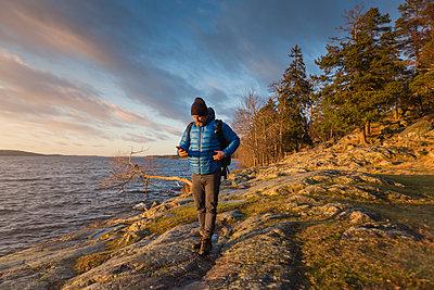 Man walking along coastline in Jarfalla, Sweden - p352m1536583 by Calle Artmark