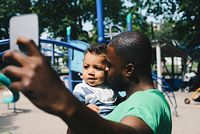 Father kissing toddler while taking selfie through mobile phone at park - p426m1507077 by Maskot